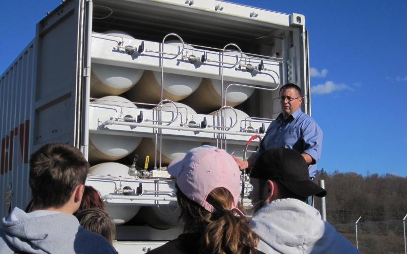 A gas company employee explains to Lehigh students how natural gas can be converted to be used as a truck fuel.